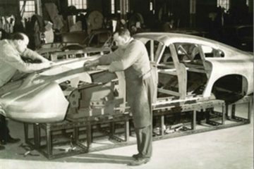 Master sheet metal worker Bert Brookes, in apron, affixes the magnesium/aluminum alloy panels to DP215 in 1963